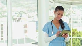 Glimlachende arts gebruikend tablet en bekijkend camera stock videobeelden