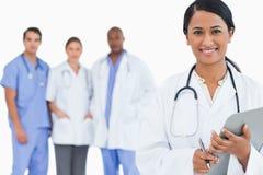 Glimlachende arts met klembord en personeelsleden achter haar royalty-vrije stock afbeeldingen