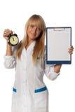 Glimlachende arts met lege klembord en klok Stock Afbeelding