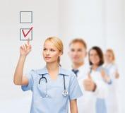 Glimlachende arts of verpleegster die aan controleteken richten Stock Foto