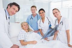 Glimlachende artsen die röntgenstraal tonen aan patiënt stock foto's