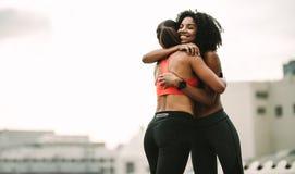 Glimlachende atleet die een omhelzing geven aan haar vriend tijdens training royalty-vrije stock foto