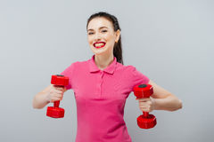 Glimlachende atletische vrouw die omhoog spieren met rode domoren pompen die op witte achtergrond worden geïsoleerd Sterk geschik royalty-vrije stock foto's