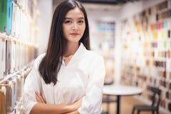 Glimlachende Aziatische bedrijfsvrouw die de materiële ruimte van het tabletverblijf kijken jonge Aziatische gelukkige directeur royalty-vrije stock foto's
