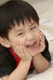 Glimlachende Aziatische jongen die op bed ligt royalty-vrije stock afbeeldingen