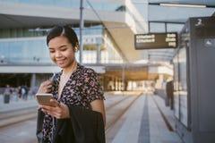 Glimlachende Aziatische student die zich bij een lezingsteksten van het trameinde bevinden stock afbeelding