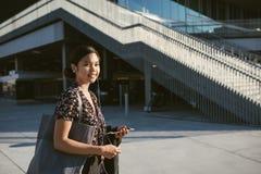 Glimlachende Aziatische universitaire student die op campus die aan muziek lopen luisteren royalty-vrije stock fotografie
