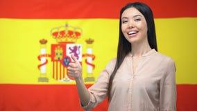 Glimlachende Aziatische vrouw die duim-op gebaar tegen Spaanse vlagachtergrond tonen stock video