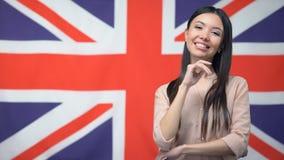 Glimlachende Aziatische vrouw die zich tegen Britse vlag, internationale vriendschap bevinden stock video