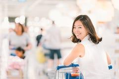 Glimlachende Aziatische vrouw met boodschappenwagentje of karretje bij warenhuis of winkelcomplex Royalty-vrije Stock Foto's