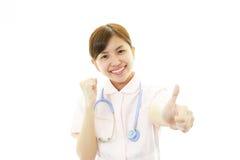 Glimlachende Aziatische vrouwelijke verpleegster met omhoog duimen Stock Afbeelding
