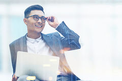 Glimlachende Aziatische zakenman met laptop en glazen Royalty-vrije Stock Foto's