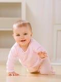 Glimlachende baby die op woonkamervloer kruipt Royalty-vrije Stock Foto's