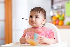 Glimlachende baby die voedsel op keuken eten stock foto's