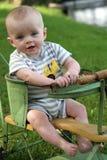Glimlachende babyjongen in antieke wandelwagenwaterkant Royalty-vrije Stock Afbeelding