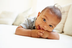 Glimlachende Babyjongen die op Buik thuis liggen Royalty-vrije Stock Foto
