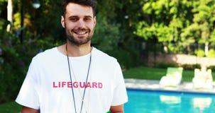 Glimlachende badmeester die op klembord bij poolside schrijven stock videobeelden