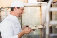 Glimlachende bakker die deeg in oven zetten stock fotografie