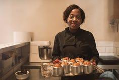 Glimlachende bakker die een dienblad van muffins in haar keuken houden royalty-vrije stock fotografie