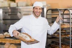 Glimlachende bakker die het brood van de cameraholding bekijken royalty-vrije stock afbeelding