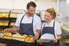 Glimlachende bakkers die blocnote en het houden van een mand met brood bekijken Royalty-vrije Stock Afbeelding