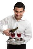 Glimlachende bediende of kelner met wijn royalty-vrije stock afbeeldingen