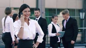 Glimlachende bedrijfs op de telefoon en haar collega's op de achtergrond spreken en vrouw die positief babbelen stock video
