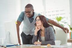 Glimlachende bedrijfsberoeps die computer bekijken terwijl het werken bij bureau stock afbeelding