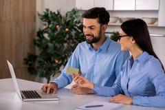 Glimlachende bedrijfscollega's die online bankwezensysteem met behulp van stock afbeelding