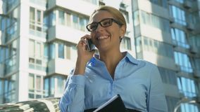 Glimlachende bedrijfsdame die in openlucht op smartphone spreken die, succesvolle overeenkomst verheugen zich stock videobeelden