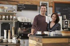 Glimlachende bedrijfseigenaars achter de teller van hun koffie royalty-vrije stock foto