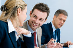Glimlachende bedrijfsmens die met collega's spreekt Stock Afbeelding