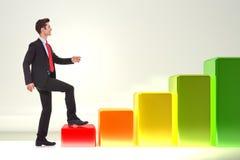Glimlachende bedrijfsmens die op een het groeien grafiek stapt Royalty-vrije Stock Foto's