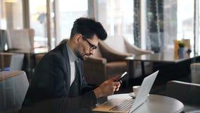 Glimlachende bedrijfsmens die wat betreft het smartphonescherm van sociale media in koffie genieten stock videobeelden
