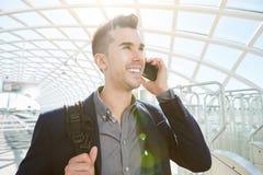Glimlachende bedrijfsmens op mobiel telefoongesprek met zak Stock Foto's