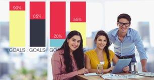 Glimlachende bedrijfsmensen bij bureau door grafieken Stock Foto
