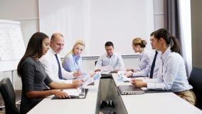 Glimlachende bedrijfsmensen die in bureau samenkomen stock video