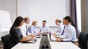 Glimlachende bedrijfsmensen die in bureau samenkomen stock footage