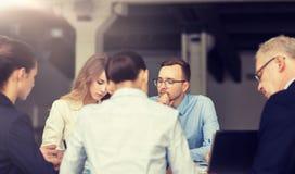 Glimlachende bedrijfsmensen die in bureau samenkomen royalty-vrije stock foto