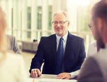 Glimlachende bedrijfsmensen die in bureau samenkomen stock foto
