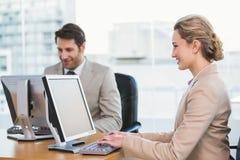 Glimlachende bedrijfsmensen die computer met behulp van Royalty-vrije Stock Foto