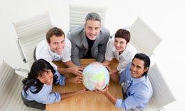 Glimlachende bedrijfsmensen die een bol houden Stock Afbeeldingen