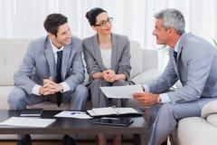 Glimlachende bedrijfsmensen die en op bank samenwerken spreken stock afbeelding