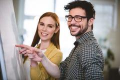 Glimlachende bedrijfsmensen die op whiteboard richten Royalty-vrije Stock Fotografie