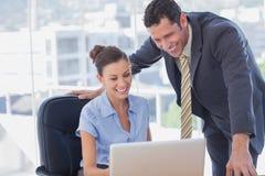 Glimlachende bedrijfsmensen die samen met zelfde laptop werken royalty-vrije stock afbeeldingen