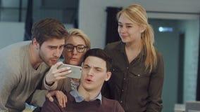 Glimlachende bedrijfsmensen die selfie in vergaderzaal op creatief kantoor nemen stock video