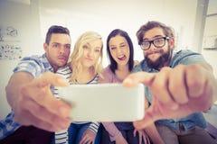 Glimlachende bedrijfsmensen die voor selfie stellen Stock Foto