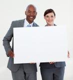 Glimlachende bedrijfsmensen die witte kaart houden stock foto