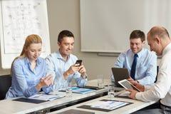 Glimlachende bedrijfsmensen met gadgets in bureau Royalty-vrije Stock Afbeeldingen
