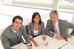 Glimlachende bedrijfsmensen rond vergaderingstablet stock afbeeldingen